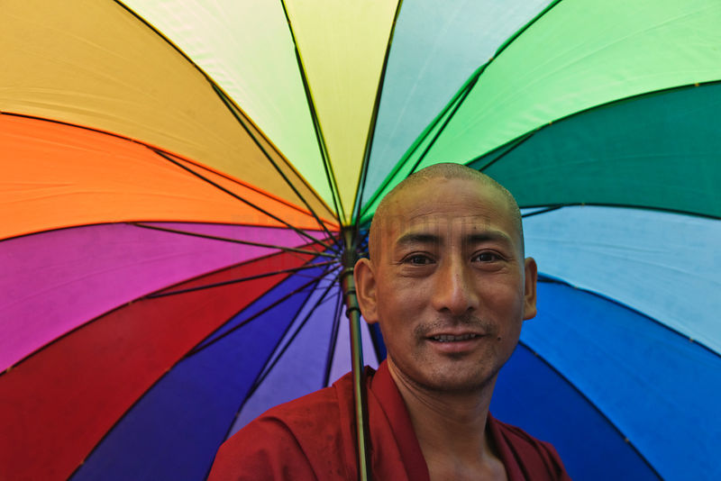 Monk with Rainbow Colored Umbrella