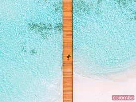 Overhead view of woman walking on jetty, Maldives