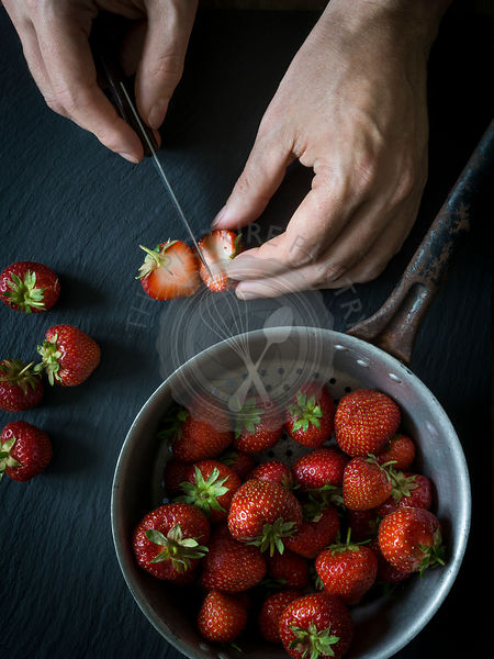 Strawberries on black slate with vintage colander and hands cutting strawberries. Top view