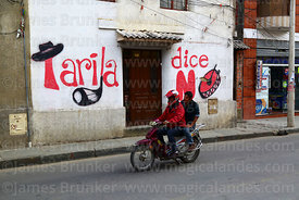 "People on motorbike riding past ""Tarija Says No"" political mural on house, Tarija, Bolivia"