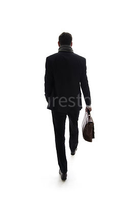 A mystery man in a suit, walking away and carrying a bag, in Semi-silhouette – shot from eye level.
