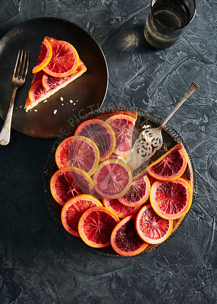 Moody blood orange cake with slices of  poached blood oranges on top in a sugar syrup.