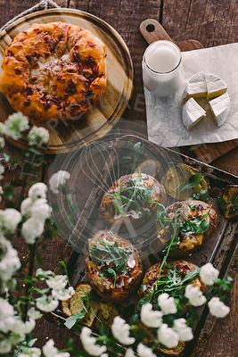 Baked stuffed potatoes with cheese, vegetables, sour cream and rucola on wooden table. Top view
