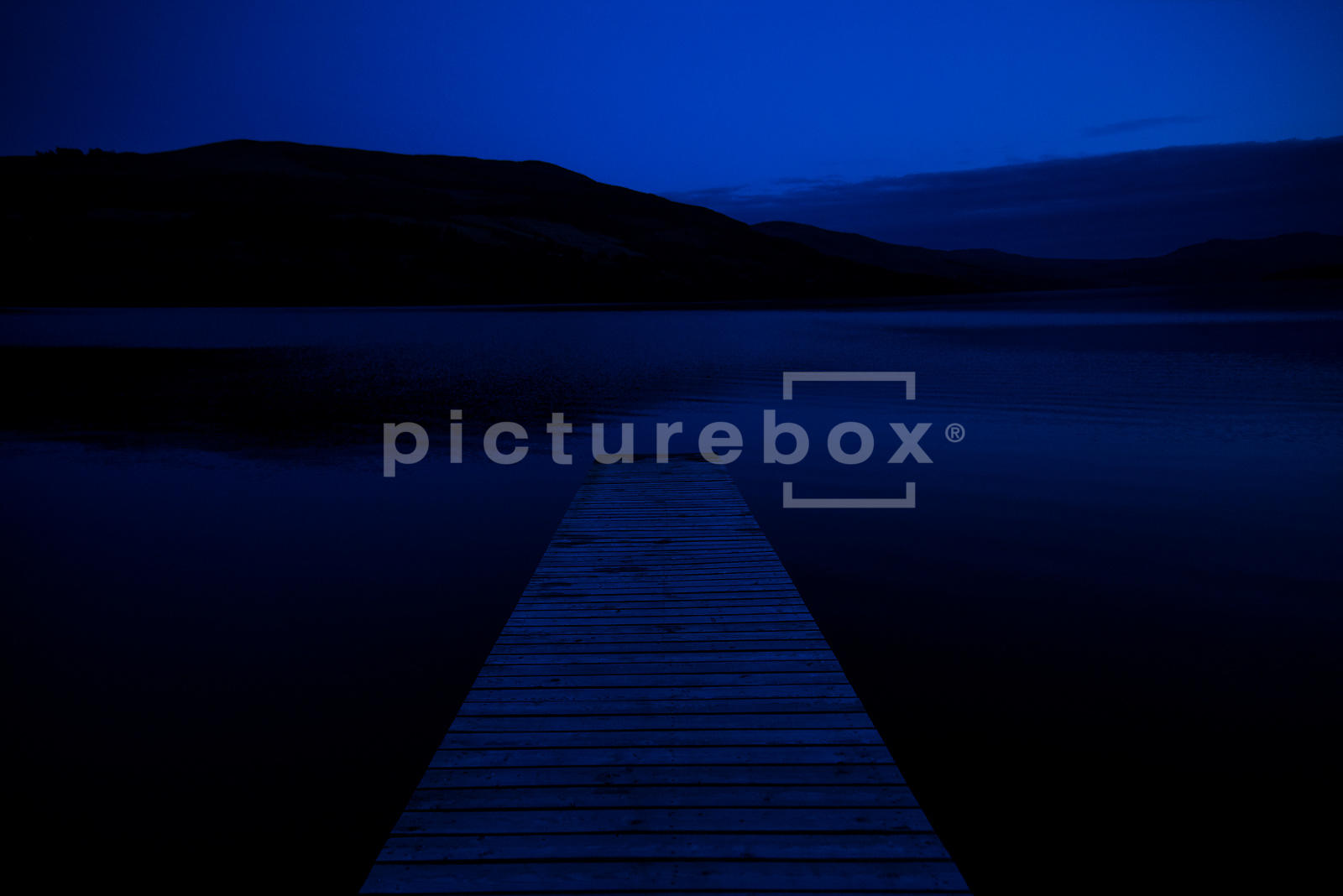 An atmospheric image looking out over a lock / lake, with a wooden Jety in the foreground, at night.
