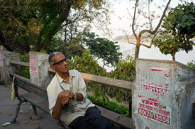 India - Chandannagar - An old man sits on a bench on the Strand overlooking the Hoogley River