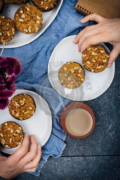 Two women grabbing banana nut muffins for a quick breakfast photographed from top view. A cup of coffee and flowers accompany.