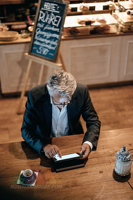 Senior businessman sitting cafe, using digital tablet