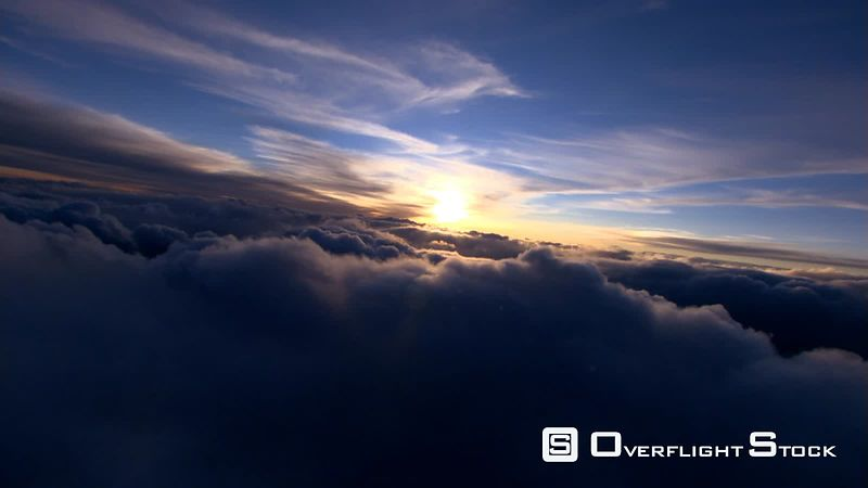 Flying through clouds toward setting sun
