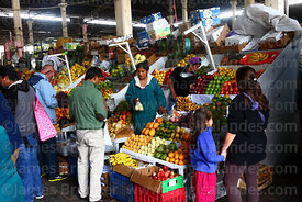 People buying fresh fruit from stall in San Pedro market, Cusco, Peru