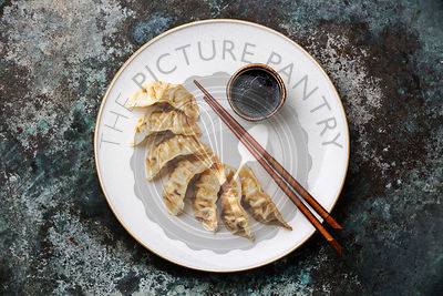 Gyoza dumplings on plate, chopsticks and soy sauce on metal background