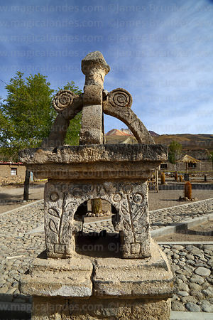 Unusual carved stone cairn in village square, Tunupa volcano in background, Coquesa, Bolivia