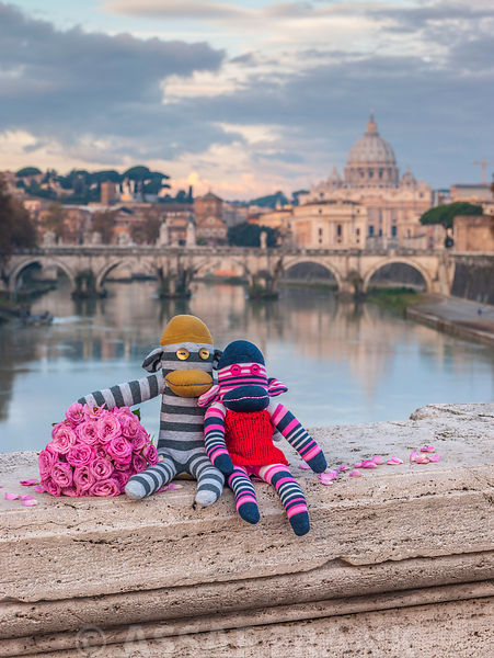 Monkeys with bunch of roses on bridge near Basilica di San Pietro in Vatican, Rome, Italy