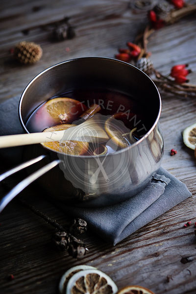 Hot winter drink. Mulled wine with orange, lemon and spices in a casserole on wooden rustic table. Chrismas atmosphere