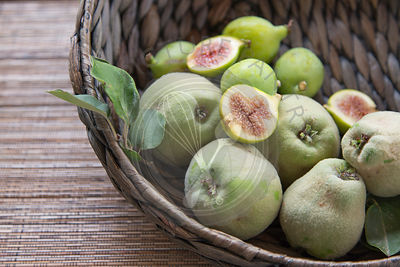 quinces and figs in woven basket with cut figs on top