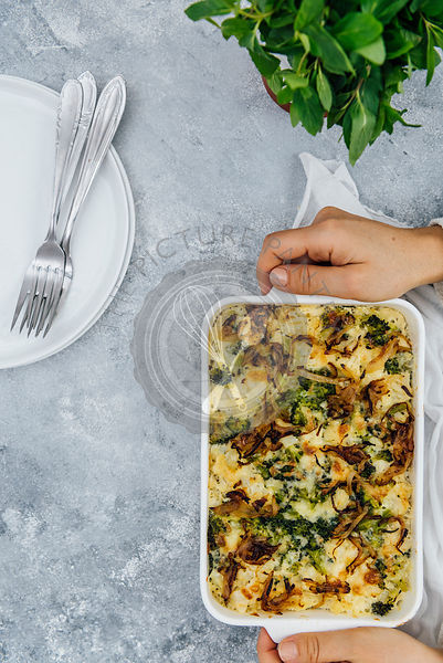 A woman serving a vegetarian cauliflower and broccoli casserole in a pan photographed from top view. Fresh herbs, white plates and forks accompany.