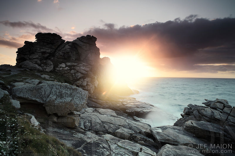 Dramatic sunset over rocky sea shore