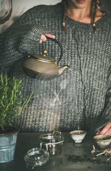 Female in sweater pouring green tea from pot