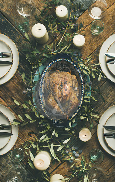 Flat-lay of whole roasted chicken in tray for Christmas eve celebration, plates, glasses and candles over rustic wooden background