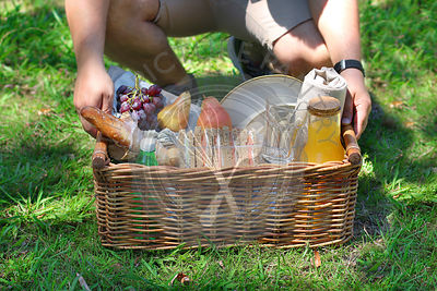 Young male holding a picnic basket with  food and drinks