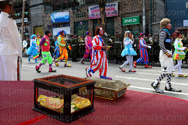Clowns parade past the remains of Eduardo Abaroa during official events for Dia del Mar / Day of the Sea, Plaza Avaroa, La Paz , Bolivia