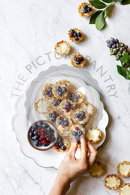 Lemon Blueberry Mini Tarts on a marble background