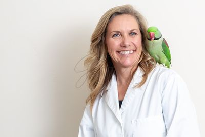 Friendly Female Veterinarian With Bird on Shoulder
