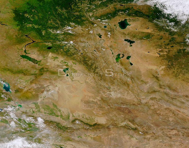 EARTH Central Asia -- The rugged and remote Altai Mountains (running diagonally from the upper left to lower right of the image) tower over the surrounding basin of desert, steppe, forest, and taiga ecosystems.