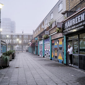 In the early morning mist of dawn, Jason Patterson opens the shutters at Maureen's Pie and Mash shop, Poplar, London