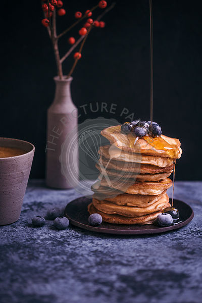 Stack of pancakes with maple syrup drizzle and blueberries