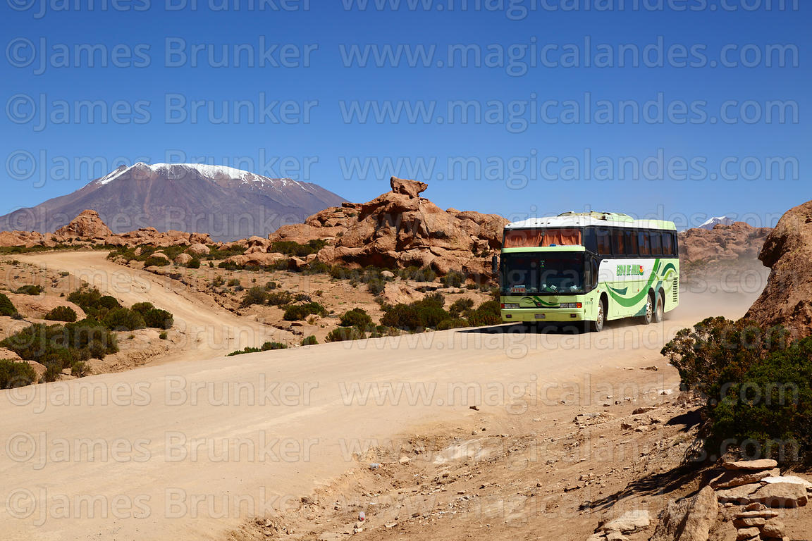 Calama to Uyuni bus on Route 701 passing eroded volcanic rock formations, Cerro Caquella volcano in background, Nor Lípez Province, Bolivia