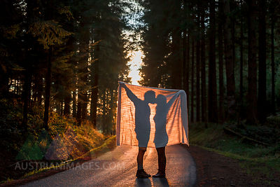 Silhouette of couple holding blanket kissing on country road in forest