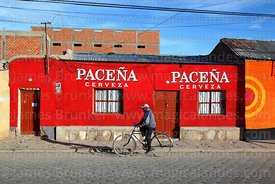 Man cycling past Paceña beer mural on house, Uyuni, Bolivia