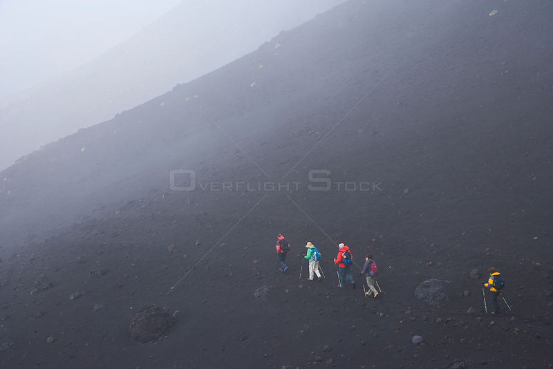 Hikers climbing Mount Etna in the mist, Etna, Sicily, Italy, October 2007
