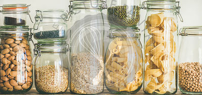 Various uncooked cereals, grains, beans and pasta for healthy cooking in glass jars on wooden table