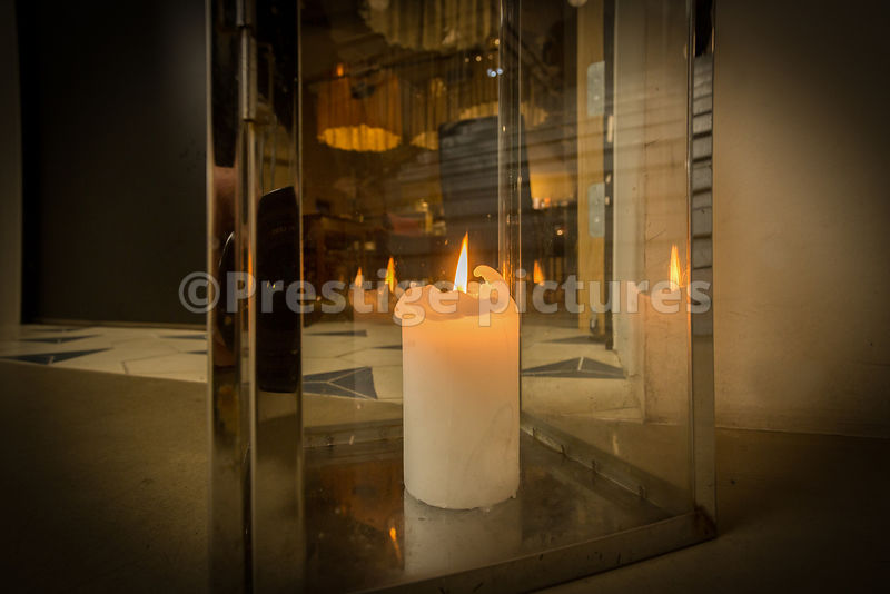 Chunky candle burning inside a glass housing on the floor