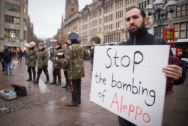 Alleppo Bombing Protestor looking in the Camera at the Hamburg Rathausmarkt Christmas Market