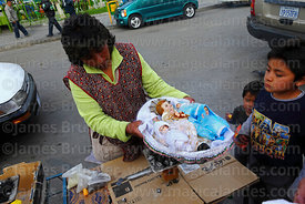 Woman blessing baby Jesus figure with incense on street outside church during Reyes (Epiphany, January 6th), La Paz, Bolivia