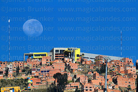 Nearly full waning moon setting behind Yellow Line cable car terminal in Ciudad Satelite (El Alto) and houses on hillside, seen from La Paz, Bolivia