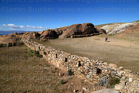Inca wall and tourist visiting the Sacred Rock / Titikala in Sanctuary area near Chincana ruins, Sun Island, Lake Titicaca, Bolivia