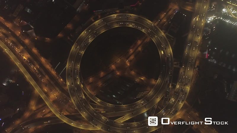 Circular Illuminated Elevated Nanpu Highway at Night. Shanghai, China. Aerial Vertical View. Drone is Flying Downward and Spinning Around. Establishing Shot.