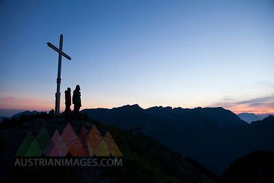Austria, Tyrol, two hikers standing at summit cross