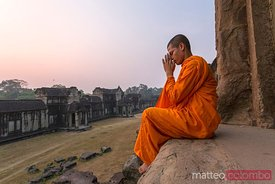 Buddhist monk praying inside Angkor Wat temple, Cambodia