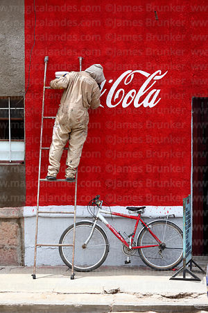 Man painting Coca Cola logo on wall of building, Uyuni, Bolivia