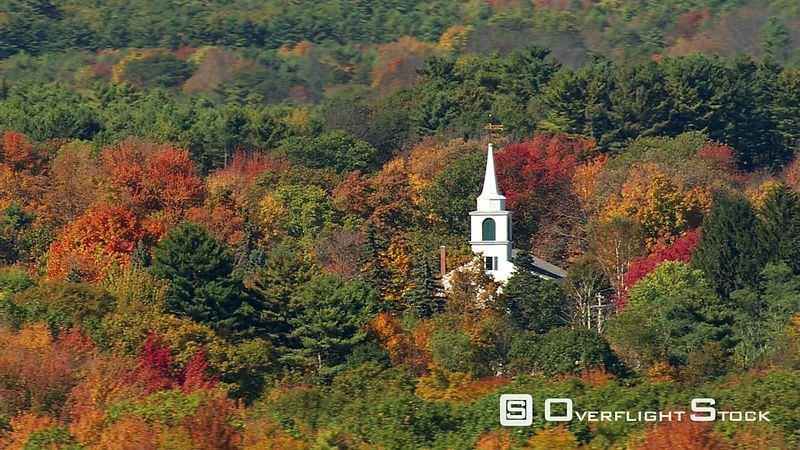 Low flight passing church amid New England autumn woods