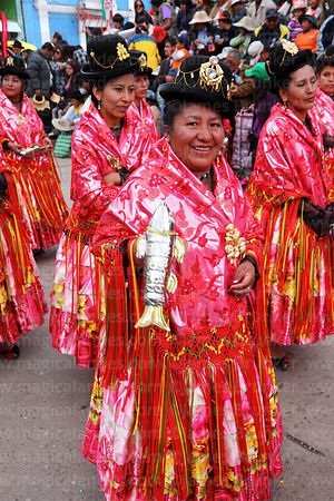 Cholita holding silver fish shaped rattle dancing the morenada at Virgen de la Candelaria festival, Puno, Peru
