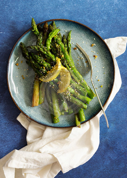 Chargrilled asparagus spears on a plate garnished with lemon slices and pistachio dukkah.