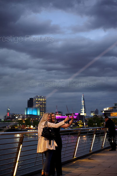 Two Young Women laughing as they take a Selfie on Waterloo Bridge at Night