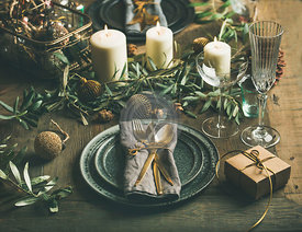 Christmas or New Years eve holiday table setting. Plates, silverware, glassware, candles, olive branches and toy festive decorations over vintahge table background, selective focus