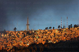 Dramatic clouds over houses on hillside and radio masts in Ciudad Satelite in El Alto, seen from La Paz, Bolivia