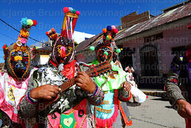 Kusillo wearing colourful mask playing charango at Virgen de la Candelaria festival, Puno, Peru